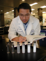 Technician in lab coat examines samples